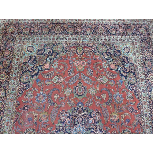 131 - A Persian Kashan carpet, central floral medallion and stylised floral motifs on a rouge field, withi...