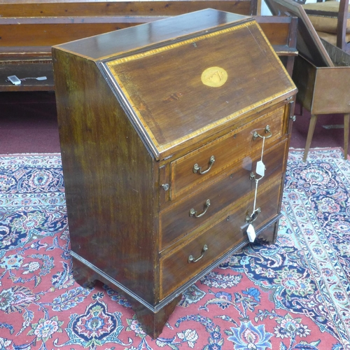 156 - An Edwardian Sheraton Revival inlaid mahogany bureau, with shell paterae to slope, having fitted int...