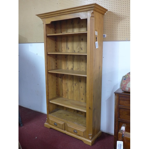 165 - A 20th century pine bookcase, having two small drawers, on bracket feet, H.198 W.107 D.38cm...