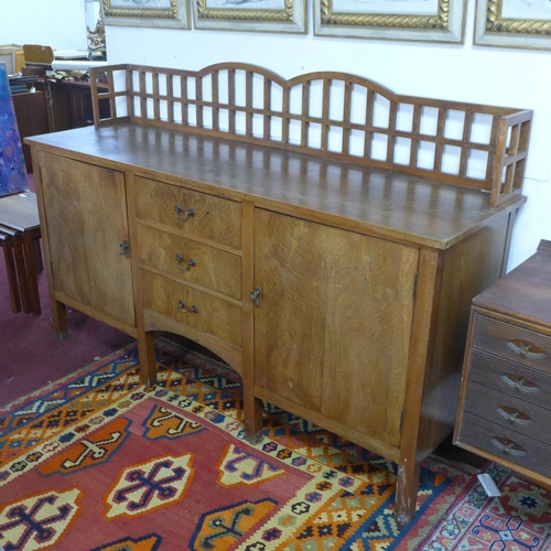 177 - A mid 20th century walnut sideboard, having gallery back above three central drawers flanked by two ...