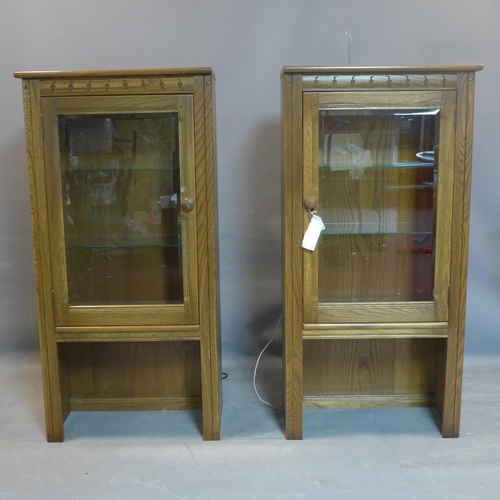 181 - A pair of mid century Ercol teak cabinets, having bevelled glass glazed doors, bearing label, H.126 ...