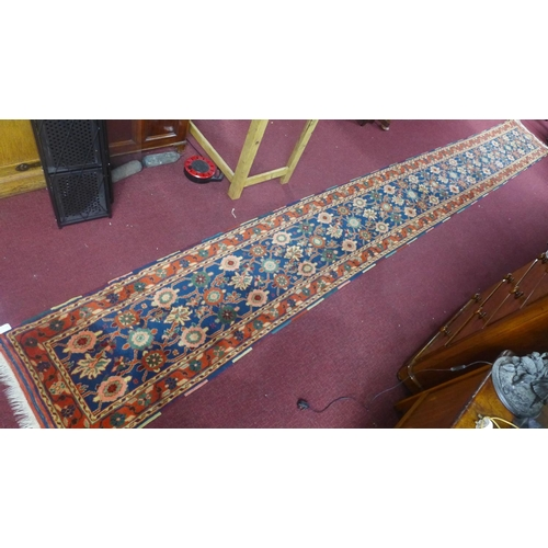 216 - A Turkish hand-made runner, with root paint, having repeating petal motifs on a dark blue ground, wi...