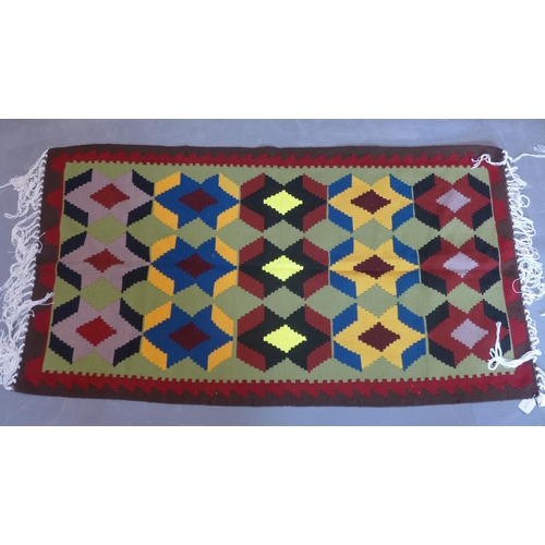 217 - A Persian hand-made kelim, repeating geometric motifs on a light green ground, 91 x 65cm...