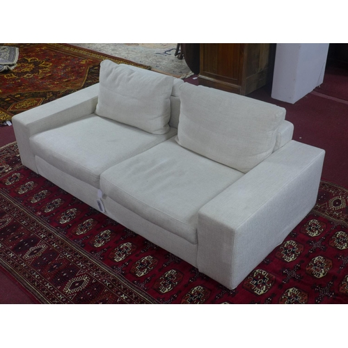 521 - A contemporary two seater sofa with cream upholstery, with four cushions, H.60 L.202 D.98cm...