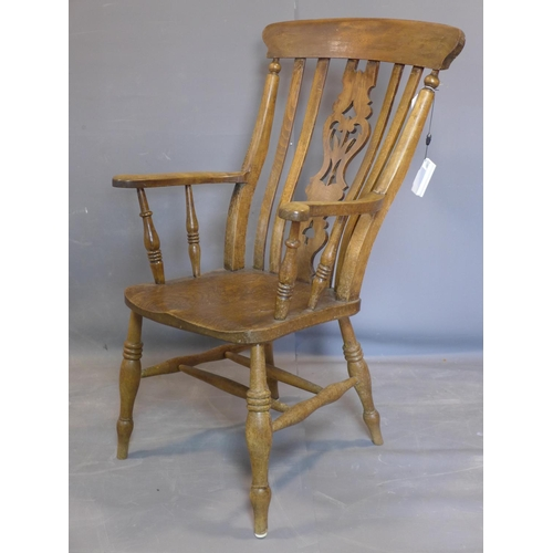 523 - A large mid 19th century elm Windsor carver chair, on turned legs joined by stretcher, H110cm, W62cm...