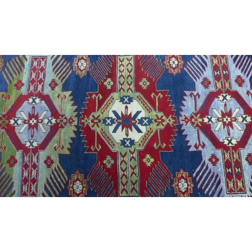 531 - A Russian Shirvan rug, triple geometric medallions and floral motifs on a blue ground, within geomet...