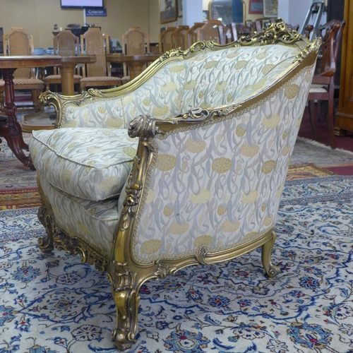 546 - A pair of giltwood armchairs, with elaborate c-scroll and floral carved giltwood frames, on c-scroll...