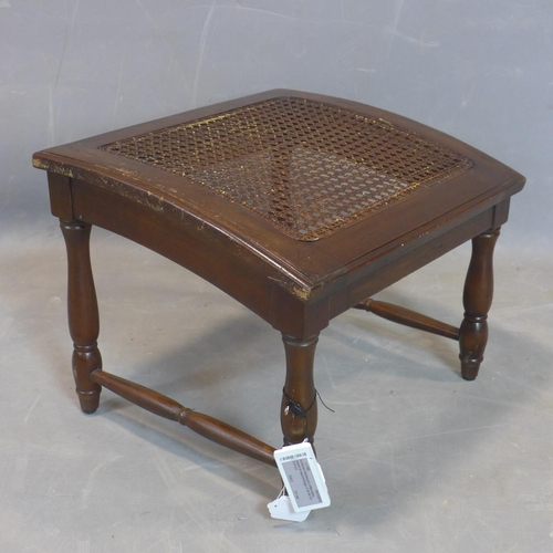 575 - An early 20th century mahogany sloped stool, with caned seat, raised on turned legs joined by stretc...