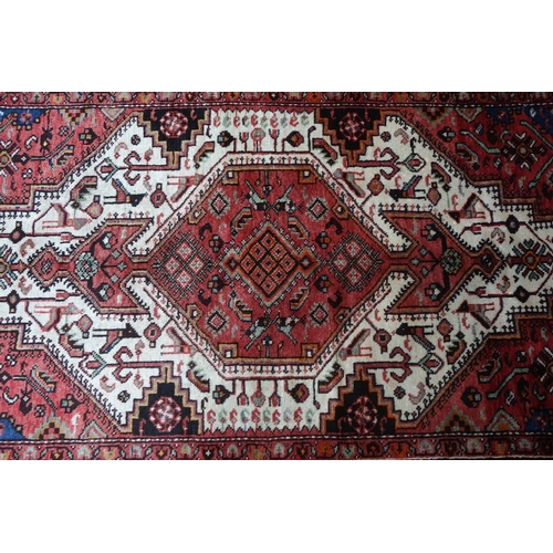610 - A North West Persian Koliai rug, central double pendant diamond medallion with repeating petal motif...