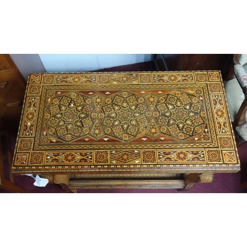 312 - An early 20th century Syrian marquetry inlaid fold over games table, H.80 W.86 D.44cm...