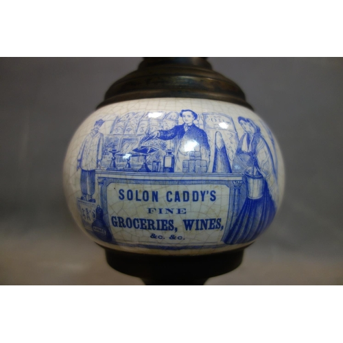 569 - A ceramic and brass oil lamp, with opaque glass shade, with advertising for Solon Caddy's Fine Groce...