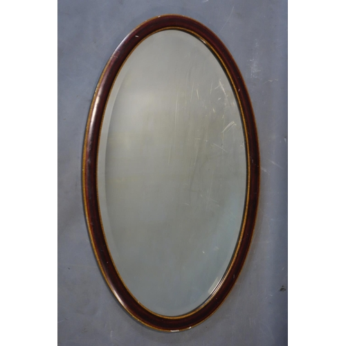 594 - An Edwardian mahogany oval mirror with satin wood inlay and bevelled plate, 74 x 44cm...