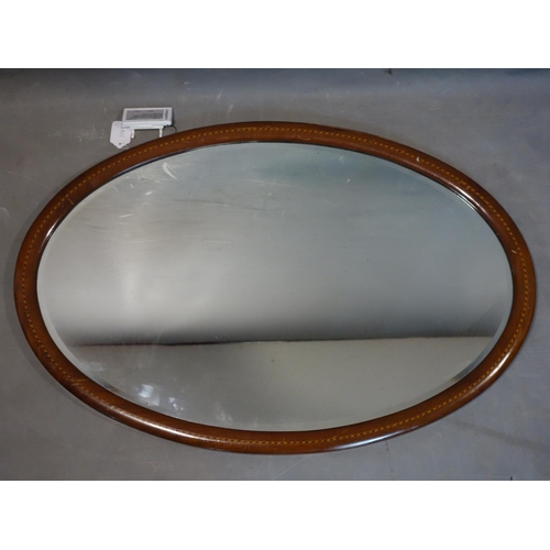 597 - A mahogany inlaid oval wall mirror, with bevelled glass plate, 60 x 89cm...