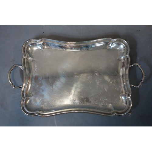 516 - An early 20th century silver tray with scalloped edge and twin handles on four feet, by William Hutt...