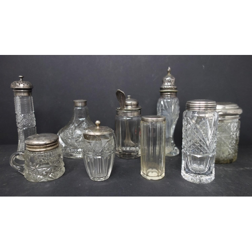 518 - A collection of cut glass salts, pepperettes and bottles, together with cut glass salts with silver ...