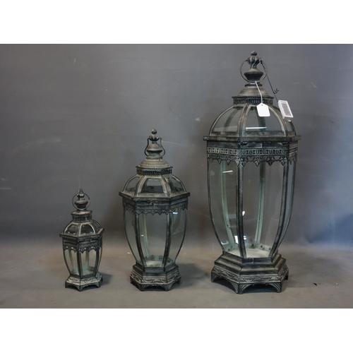 578 - Three storm lanterns of graduating size, tallest H.79cm, one glass panel broken to tallest lantern...
