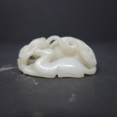 22 - A 19th century Chinese white jade carving of a mythical beast and offspring, with pierced scrolling ...