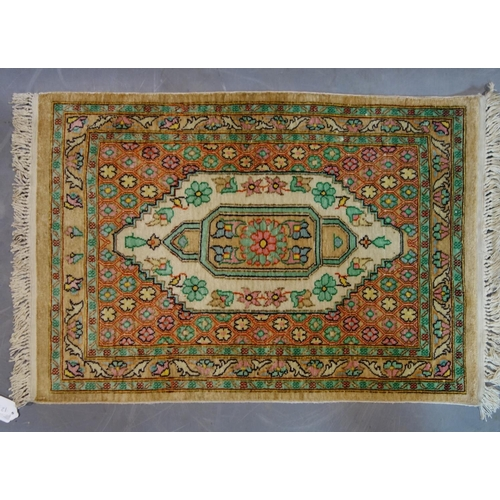269 - A Persian silk mat with lozenge medallion, on a beige ground, 72 x 49cm...