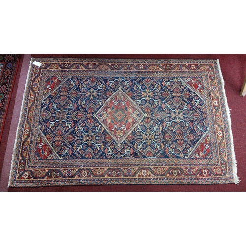 271 - A Persian Qashqai rug, central diamond medallion and floral motifs on a dark blue ground, within mul...