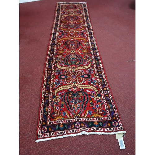 274 - A Northwest Persian Sarouk runner, repeating stylised floral motifs on a rouge field, complimented b...