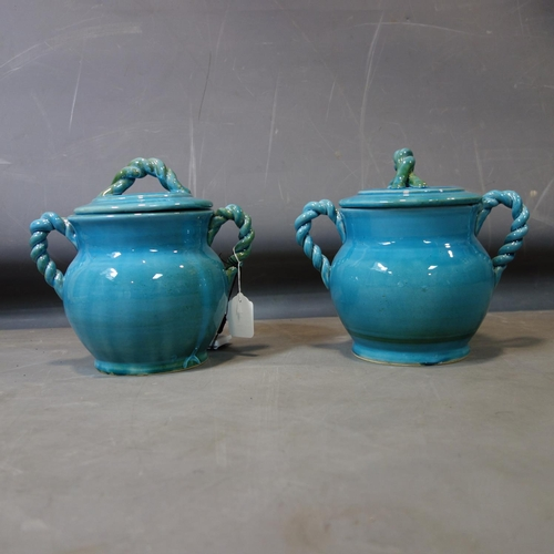 570 - A pair of Persian cyan glazed pots and covers, with rope twist design handles, H.26 W.28cm...