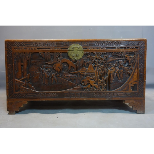 543 - An early 20th century Chinese camphor wood trunk, profuseley carved, H.55 W.101 D.50cm...