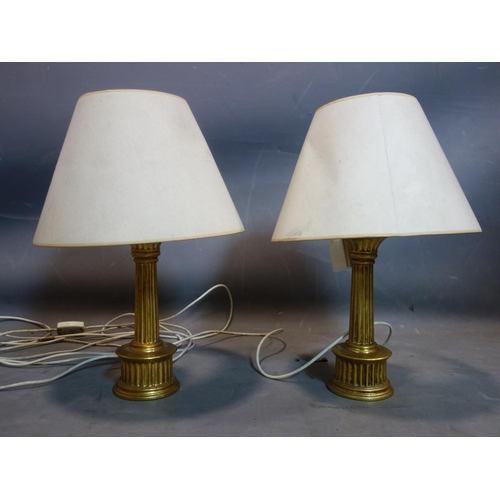 104 - A pair of gilt porcelain table lamps with shades...