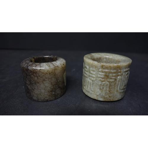 32 - Two Chinese jade scholars rings, H.2.5cm each, together with three Chinese hardstone scholars rings,...