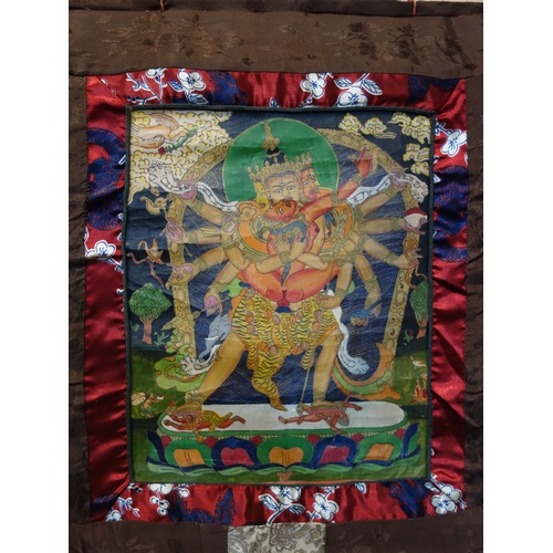 21 - A hand-painted Tibetan Thangka depicting a deity in a landscape scene with animals, having script to...