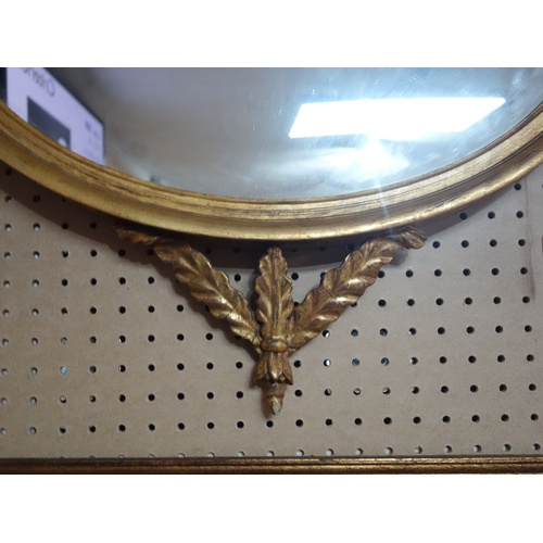 42 - A Regency carved giltwood mirror, with eagle and floral surmount, having oval glass plate, 100 x 66c...