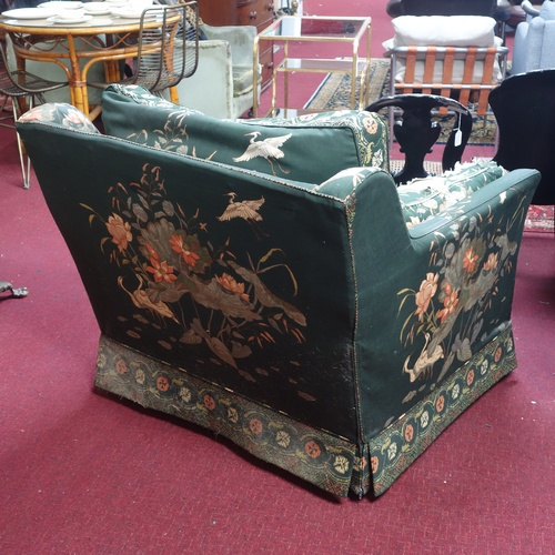 259 - A 20th century armchair, the upholstery decorated with flowers and birds, raised on castors (damage ...