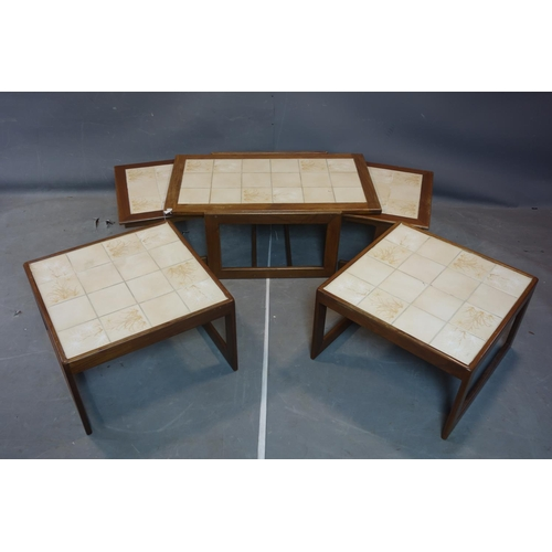 270 - A 20th century teak nest of table with tiled tops, together with a pair of matching coffee tables...