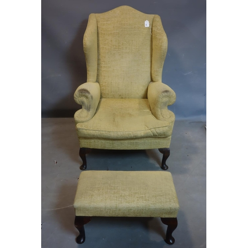 266 - A Georgian style wing back armchair, with matching stool...