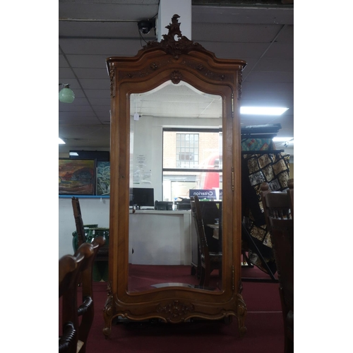 143 - An early 20th century French walnut armoire, with carved crest and bevelled mirrored door, H.238 W.1...