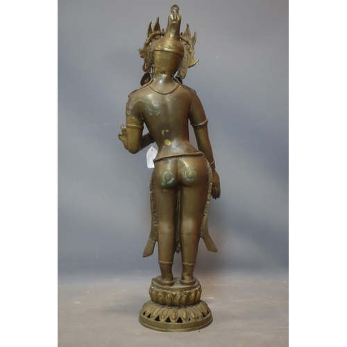 30 - A Southeast Asian brass figure of a female deity on a lotus base, H.78cm...