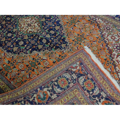 300 - A Persian Tabriz carpet, central diamond medallion on an orange ground within stylised floral border...