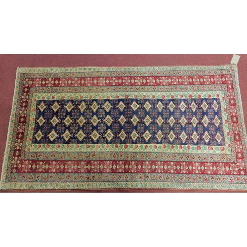 184 - A north east Persian Turkoman rug, the repeating stylised tokeh motifs, on a sapphire ground, contai...