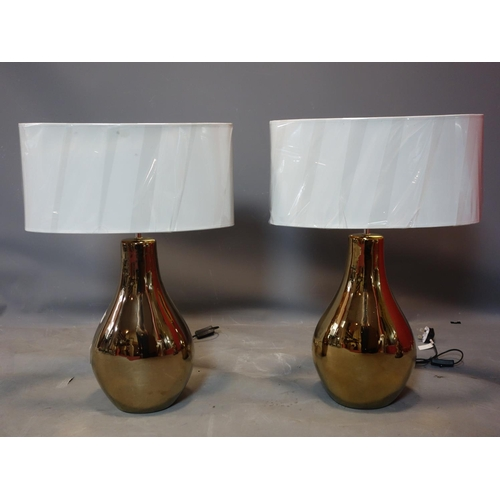 333 - A pair of contemporary gilt table lamps, with oval cream shades, H.68cm...