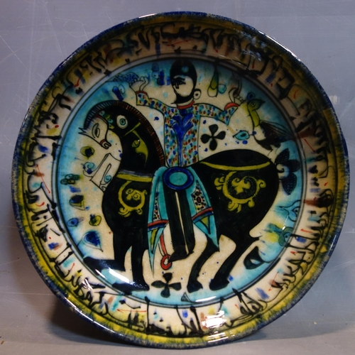 26 - A Persian glazed ceramic bowl, decorated with a figure on horseback, date and mark to base, H.7cm Di...