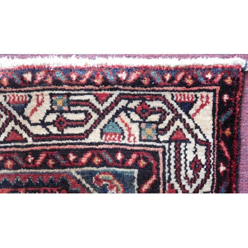 69 - A Persian Malayer runner, repeating heratie motifs on a terracotta field within stylised multifloral...