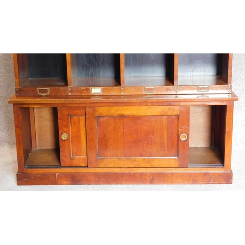47 - A mahogany two section estate cupboard fitted pigeon holes and stationery sections, makers label to ...