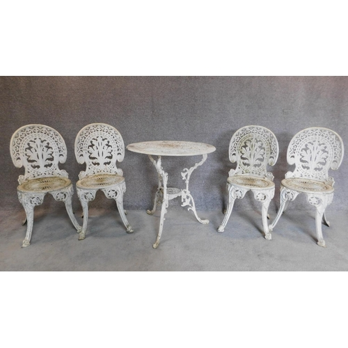 151 - A Colebrookdale style white painted garden table and 4 matching chairs. H.84cm...