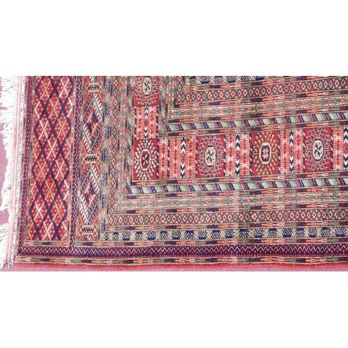 77 - A 20th century Bokhara carpet with repeating geometric gull motifs, on a red ground, contained by ge...
