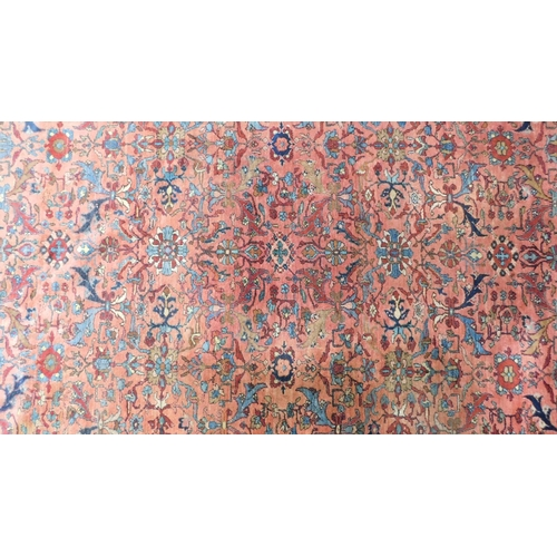 78 - A large Persian rug with repeat motifs on a rouge back ground surrounded by a stylised floral and ge...