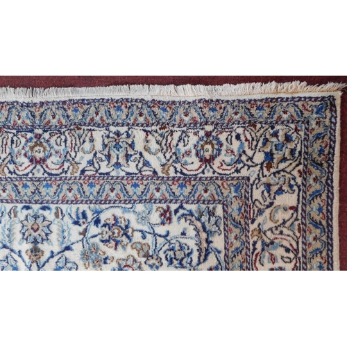 79 - A part silk Nain Isfahan rug with repeating spandrels and petal motifs on an ivory field surrounded ...