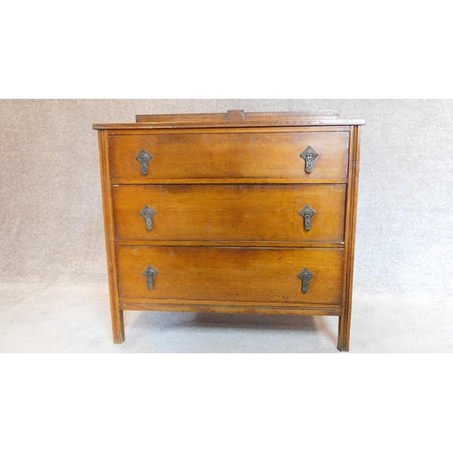 38 - A mid 20th century oak three drawer chest with brass handles and carved back. H.89 W.91 D.46cm...
