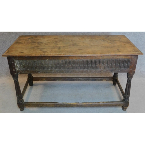 48 - A 17th century oak console table with later top above carved frieze with turned stretchered supports...
