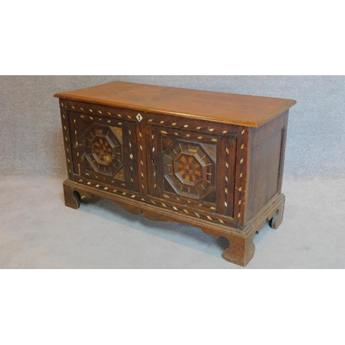 49 - A bone inlaid oak coffer with hinged lid and pair of panel doors on bracket feet. 55x116x50cm...
