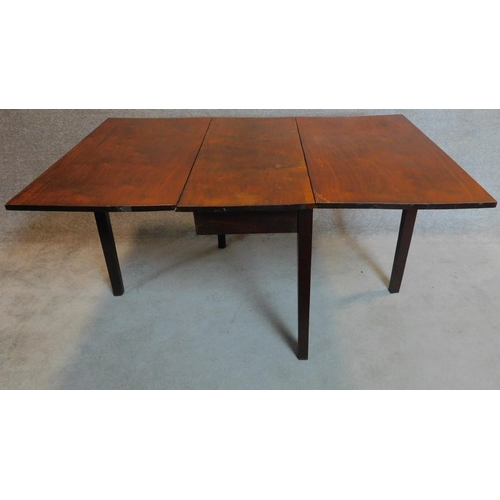 15 - A Georgian mahogany drop flap dining table on square section supports. 73x148x99cm...