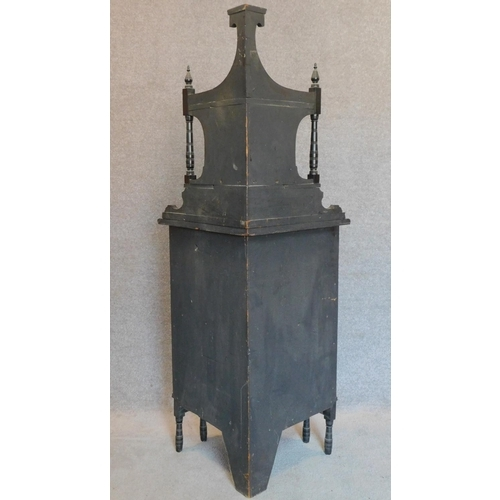 17 - A late 19th century ebonised corner cabinet with mirrored back and carved panels in the aesthetic ma...